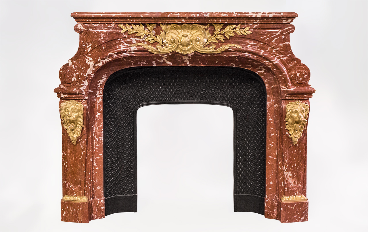 This extraordinary antique fireplace was inspired by the one in the Meeting room of the Fenaille mansion created by Maurice Fenaille in Severac le Chateau, South of France, in 1912.Made out of Red languedoc marble, this fireplace is garnished with sublime gilt bronze ornaments with lions heads and a large foliaged shell.Louis XIV style , this fireplace is inspired from the fireplace which is in the Salon of Hercule in the Versailles Palace.Both sides of this fireplace are ornated with bronze and are paneled.