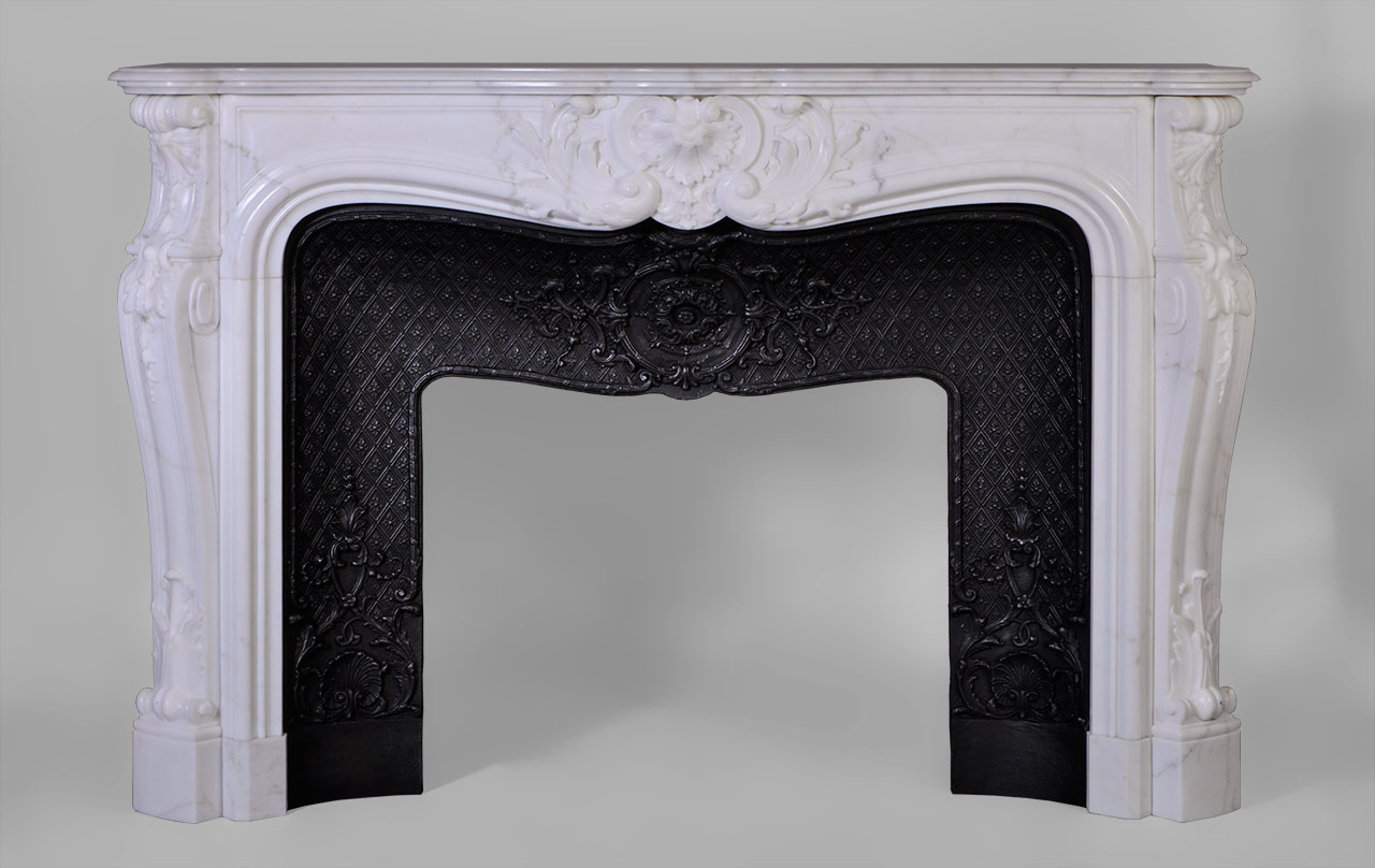 Louis XV style, the carved decoration of this fireplace is extremely elaborate. A large reversed foliaged shell adorns the center of the frieze. Jambs are   curved and have a winding lined with fleshy acanthus leaves in the lower part. The top of the jambs are ornated with carved shells and bells fall.This fireplace is equipped with a beautiful cast iron insert adorned with scrolls, shells and foliage medallions .
