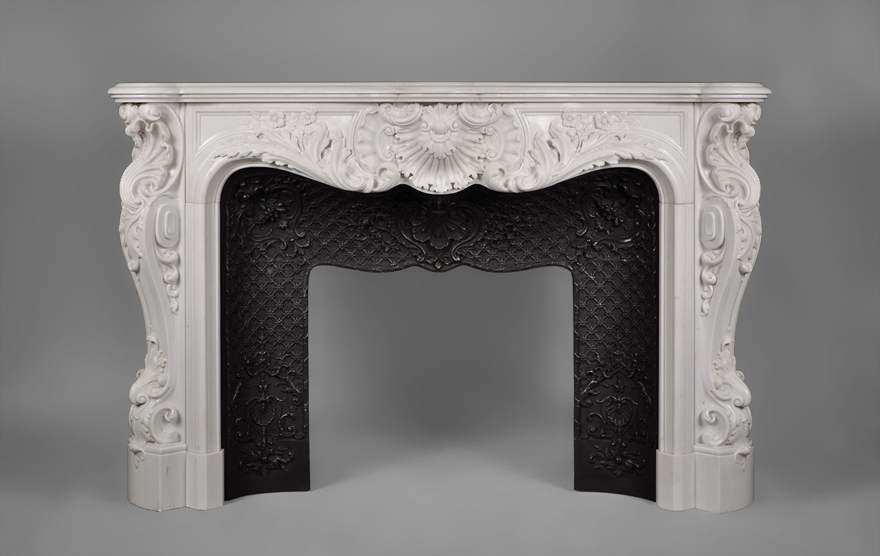 This richly and intricately carved Louis XV style fireplace is highly opulent. Manufactured in our workshop and made out of Carrara White P marble.Both the front and the scrolled angled jambs are carved with floral and rocaille ornaments. The central cartouche is decorated with boldly shell and acanthus foliage.