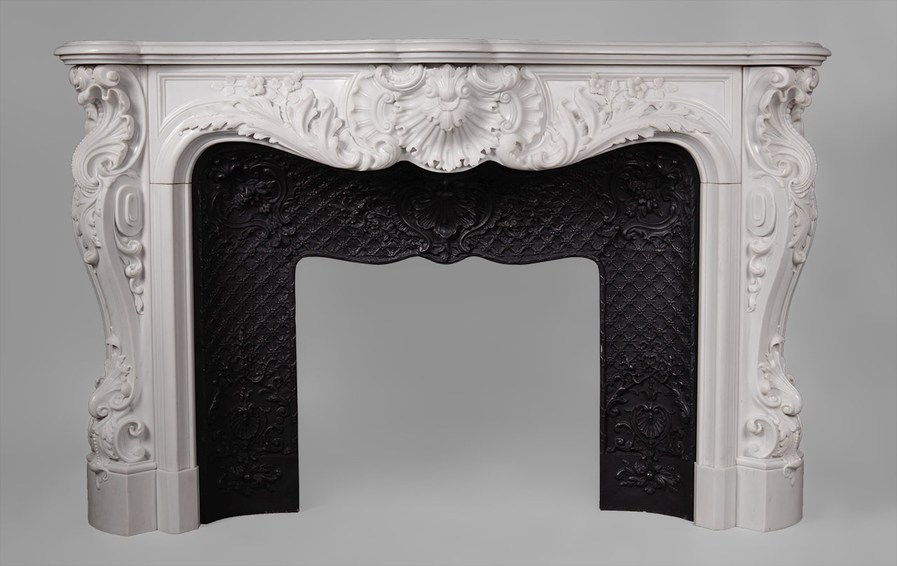 This richly and intricately carved Louis XV style fireplace is highly opulent. Manufactured in our workshop and made out of Carrara semi-statuary marble.Both the front and the scrolled angled jambs are carved with floral and rocaille ornaments. The central cartouche is decorated with boldly shell and acanthus foliage.