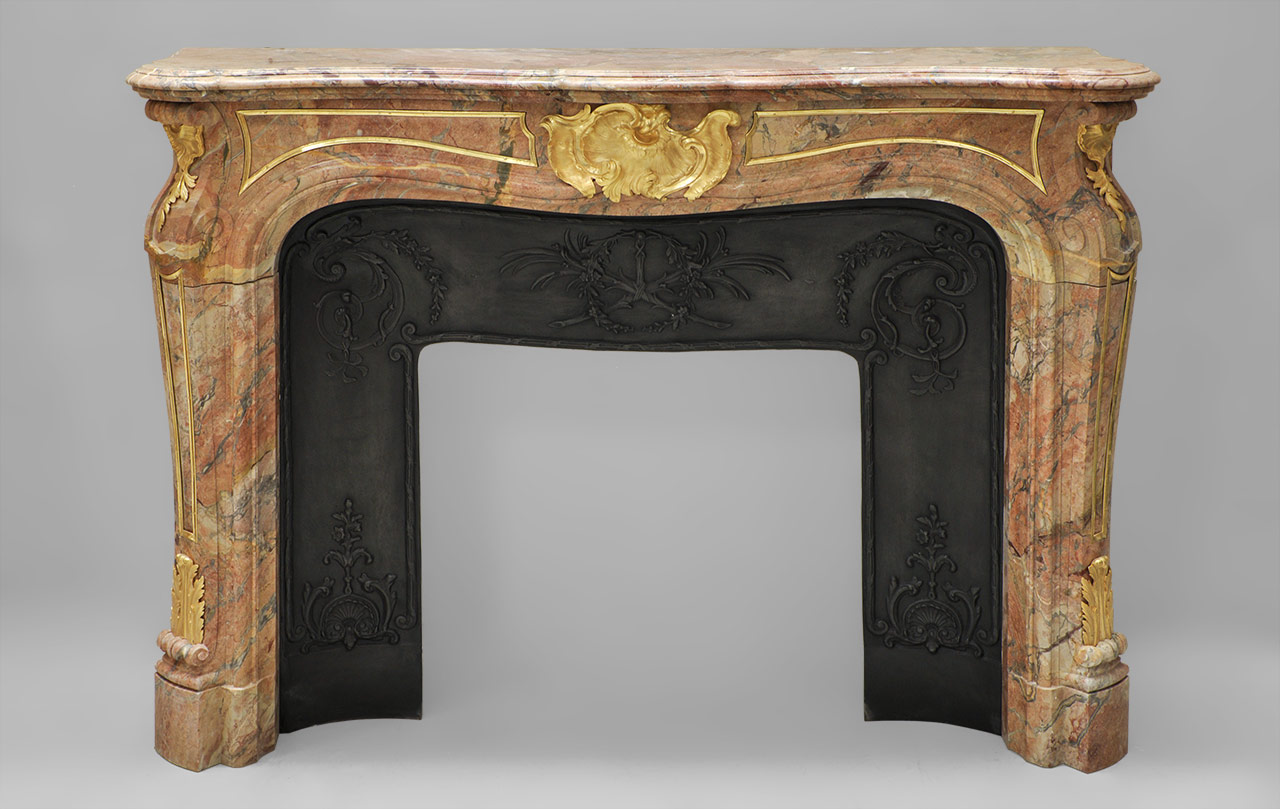 """Comtesse de Vintimille"" is a rare Sarrancolin Fantastico marble fireplace mantel with gilded bronze ornaments. This Louis XV style fireplace is shaped with curved contours.
